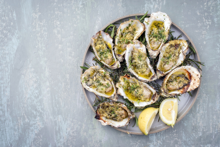 Barbecue overbaked fresh opened oyster with garlic, lemon and herbs offered as top view on a tray with copy space left
