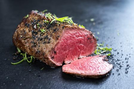 Traditionele barbecue, droog gerijpte wagyu-biefstuk van rundvlees met kruiden en specerijen gemarineerd als close-up op een zwart bord