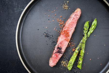 Modern barbecue dry aged wagyu flank steak sliced with green asparagus as top view plate with copy space
