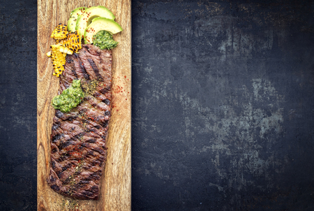 Barbecue dry aged wagyu flank steak with corn, avocado and chimichurri sauce as top view on a cutting board Stok Fotoğraf - 112275324