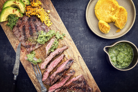 Barbecue dry aged wagyu flank steak with arepas corn, and chimichurri sauce as top view on a cutting board Stock fotó