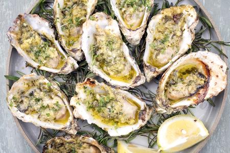 Barbacoa de ostras recién horneadas abiertas con ajo, limón y hierbas que se ofrecen como vista superior en un plato Foto de archivo