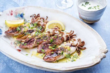 Traditional barbecue Greek calamari with herb and lemon as top view on a plate 스톡 콘텐츠