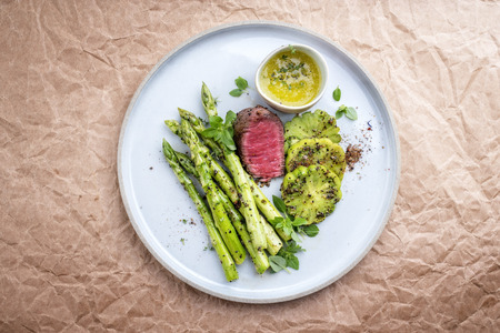 Modern barbecue dry aged sliced fillet steak with green asparagus and tomatoes as top view on a plate with copy space