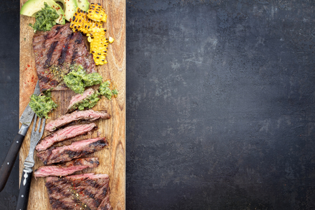 Barbecue dry aged wagyu flank steak with corn, avocado and chimichurri sauce as top view on a cutting board with copy space right