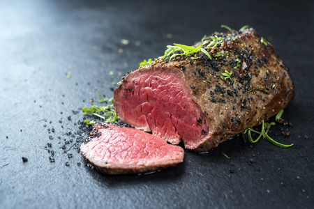 Traditional barbecue dry aged wagyu fillet steak with herb and spice marinated as closeup on a black board Stock fotó - 111675348
