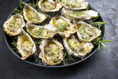 Barbecue overbaked fresh opened oyster with garlic and herbs offered as top view on a tray