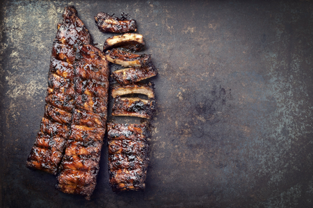 Barbecue spareribs St. Louis gesneden met hete honing chili marinade als bovenaanzicht op oud rustiek bord met kopieerruimte rechts