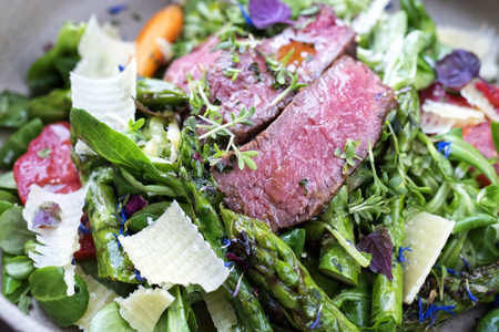 Modern spring salad with barbecue dry aged sliced fillet steak and green asparagus as closeup on a plate Stok Fotoğraf