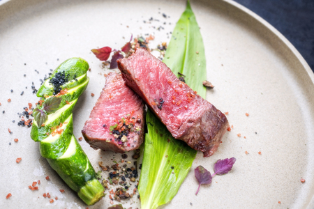 Modern barbecue dry aged sliced fillet steak with wild garlic and baby zucchini as top view on a plate with hot spices Stok Fotoğraf