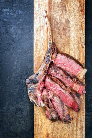 Barbecue dry aged wagyu tomahawk steak sliced as top view on a wooden board with copy space left Stock Photo