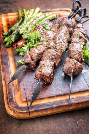 Traditional Russian shashlik on a barbecue skewer with green asparagus and paprika as close up on a burnt cutting board