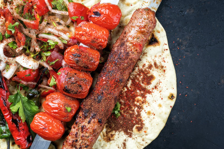 Traditional Adana Kebap skewer with tomato and salad on a flatbread with copy space right Stock Photo
