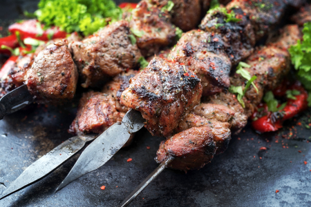 Traditional Russian shashlik on a barbecue skewer with paprika as closeup on an old board Imagens