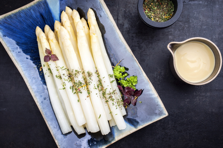 Traditional boiled white asparagus with sauce hollandaise as top view on a blue plate