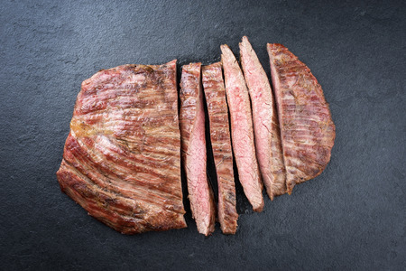 Barbecue dry aged wagyu flank steak sliced as top view on a black board