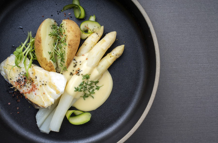 Modern German fried cod fish filet with white asparagus in hollandaise sauce und roast potatoes as top view on a plate with copy space right
