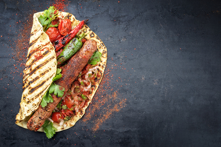 Traditional Adana Kebap with tomato and salad on a flatbread with copy space right 版權商用圖片