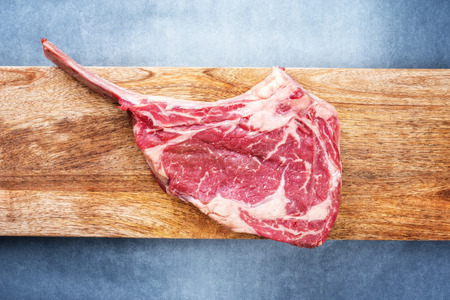 Raw dry aged wagyu tomahawk steak as top view on a wooden board with copy space