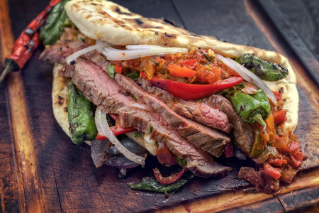 Barbecue dry aged wagyu flank steak chili relish and vegetable in a flatbread on a burnt board Stockfoto