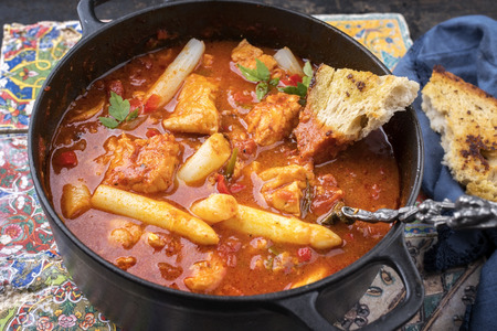 Traditional Creole cajun court bouillon with fish and gumbo chowder stew with white asparagus as top view in a pot Фото со стока - 111676517