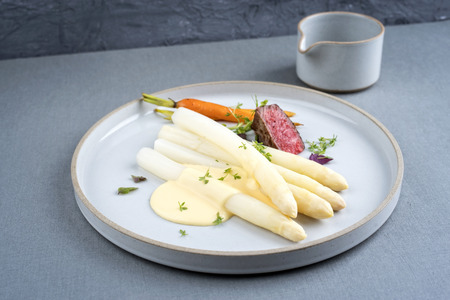 Modern barbecue dry aged sliced fillet steak with white asparagus and sauce hollandaise as closeup on a plate with copy space Stockfoto