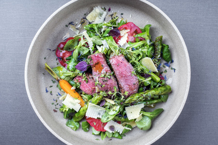Modern spring salad with barbecue dry aged sliced fillet steak and green asparagus as top view on a plate