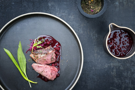 Traditional barbecue dry aged sliced venison fillet steak with wild garlic and cowberry sauce as top view on a plate with copy space Imagens