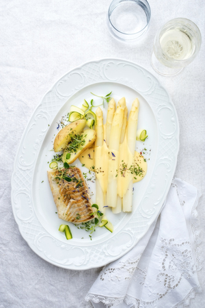 Modern German fried cod fish filet with white asparagus in hollandaise sauce und roast potatoes as top view on a plate