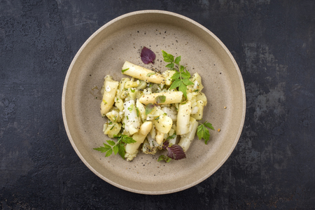 Modern style traditional German potato salad with white asparagus and gherkin as close up on a plate with copy space