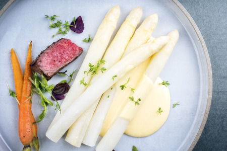 Modern barbecue dry aged sliced fillet steak with white asparagus and sauce hollandaise as closeup on a plate