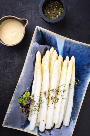 Traditional boiled white asparagus with sauce hollandaise and herbs as top view on a blue plate