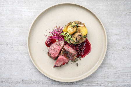 Traditional barbecue dry aged sliced venison fillet steak with potato mushroom terrine and cowberry sauce as top view on a plate with copy space