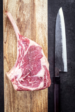 Raw dry aged wagyu tomahawk steak as top view on a wooden board with a Japanese knife