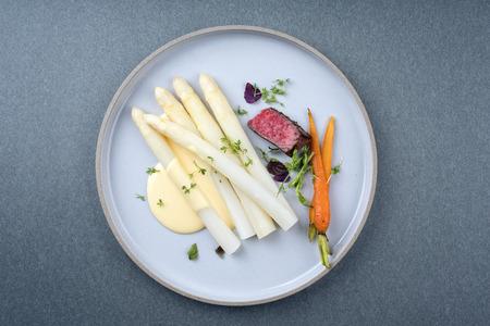 Nowoczesny grillowany stek z polędwicy w plasterkach na sucho z białymi szparagami i sosem holenderskim jako zbliżenie na talerzu z miejscem na kopię