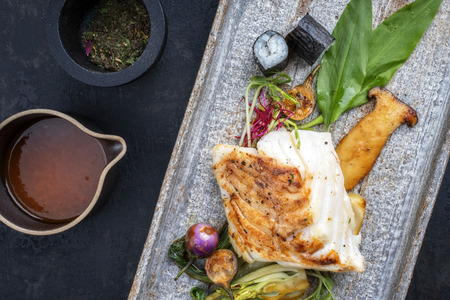Modern Japanese fried cod fish filet with bok choi and sushi rolls as top view on a plate Stock Photo