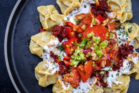 Traditional Turk manti steamed with mincemeat and paprika tomato salad as top view on a plate Stok Fotoğraf - 110761785