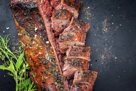 Traditional barbecue aged saddle of venison marinated as top view on an old rustic board with copy space right Stockfoto