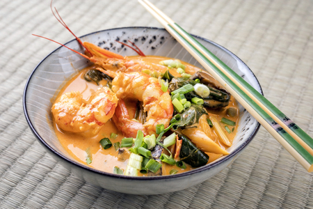 Traditional Thai kaeng phet red curry with king prawns and vegetable as top view in a bowl on place mat Stock Photo