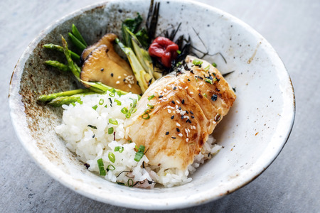 Modern Japanese fried cod fish filet with green asparagus and rice as top view in a bowl