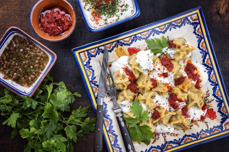 Traditional Turk manti steamed with mincemeat and paprika tomato salad as top view on a plate Stockfoto