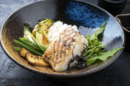 Modern Japanese fried cod fish filet with bok choi and rice as top view in a bowl Foto de archivo - 110761829
