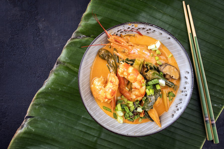 Traditional Thai kaeng phet red curry with king prawns and galgant as top view in a bowl on a banana leaf with copy space left Stock Photo