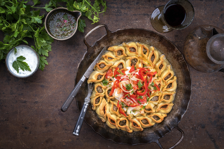 Traditional Armenian manti with mincemeat and paprika tomato salad as top view in a cast iron pan Фото со стока