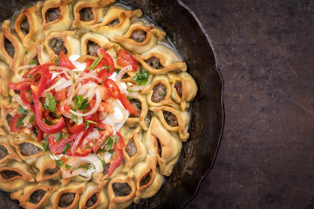 Traditional Armenian manti with mincemeat and paprika tomato salad as top view in a cast iron pan with copy space right
