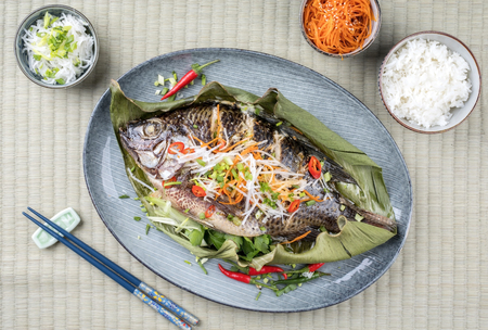 Traditional Thai barbecue tilapia fish with chili and vegetable as top view on a banana leaf