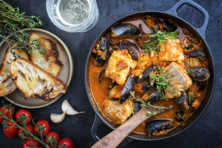 Traditional French Corsican fish stew with mussels and garlic baguette as top view in a pot