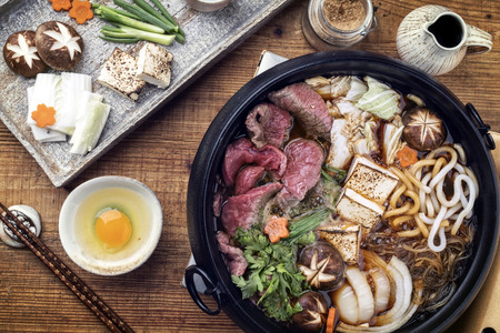 Traditional Sukiyaki pot with Kobe Beef and Vegetable as close-up on wooden table Stock Photo