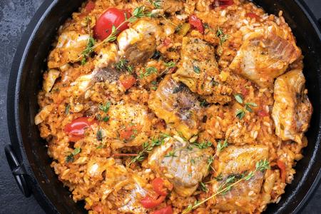 Traditional Louisiana fish jambalaya dish creole cajun with rice and tomatoes as top view in a pot