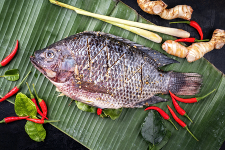 Traditional Thai barbecue tilapia fish staffed with line lemon grass and chili as top view on a banana leaf Stock Photo